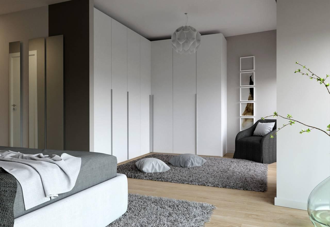 Una delle camere matrimoniali con uno spazio antistante il letto che forma una cabina armadio aperta